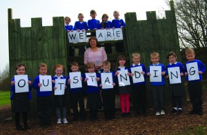 Children at John of Gaunt celebrating their 'Outstanding' Ofsted report with head teacher Fiona Chant.